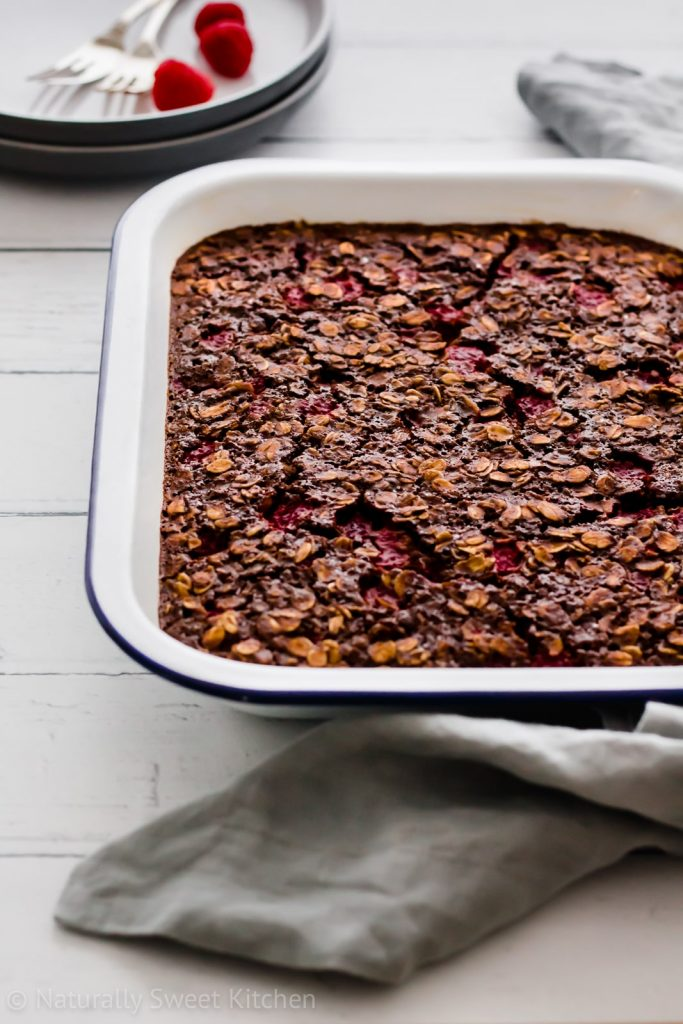This chocolate baked oatmeal recipe features tangy raspberries and a whole lot of fibre! This is a fabulous weekend brunch for a crowd. Get the recipe for this and more refined sugar free recipes at naturallysweetkitchen.com #naturallysweetkitchen #bakedoatmeal #oatmeal #raspberry #chocolate #brunch #sundaybrunch #recipes #baking #foodphotography