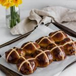 Getting ready for Easter baking? Give this easy hot cross buns recipe a go! Filled with raisins, warm cinnamon, allspice, and nutmeg, naturally sweetened with maple syrup, and topped with a honey orange glaze. Perfect for Easter brunch! Get the recipe and other refined sugar free desserts at naturallysweetkitchen.com #easter #easterbaking #baking #photography #hotcrossbuns #bread #homemade #sugarfree #refinedsugarfree #naturallysweetkitchen
