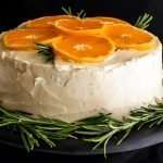 Swathes of sugar free swiss meringue buttercream covering a six inch layer orange layer cake