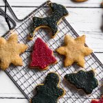 Dark green, red, and white Christmas sugar cookies on a wire rack on top of a white wooden table.