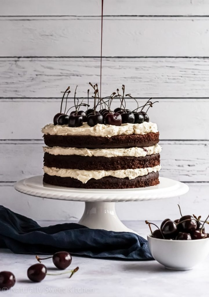 a triple layer chocolate cake being drizzled with black cherry syrup with decorative cherries in the foreground.