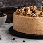 a 2 layer coffee cake on a black serving platter with coffee beans in the background and on the side