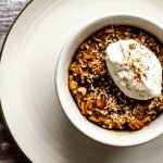 a serving of carrot cake baked oatmeal in a ramekin on an ivory plate