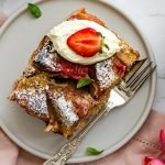 a slice of overnight strawberry french toast on an ivory plate topped with whipped cream, basil and strawberries with a coffee mug on the side