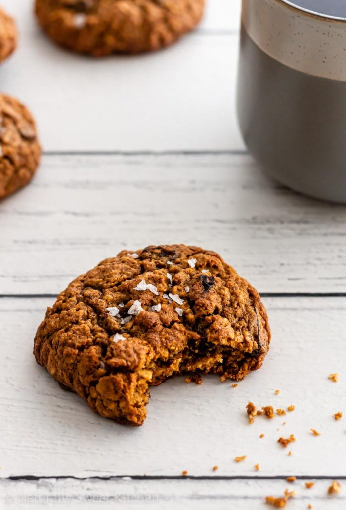 a close up shot of a bitten refined sugar free oatmeal raisin cookie on a wooden background with a cup of black coffee in the upper right hand corner