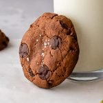 a close up shot of a chocolate chai cookie topped with sea salt leaning against a glass of milk