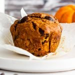 a lone pumpkin chocolate chip muffin on a white plate with the wrapper partially undone.