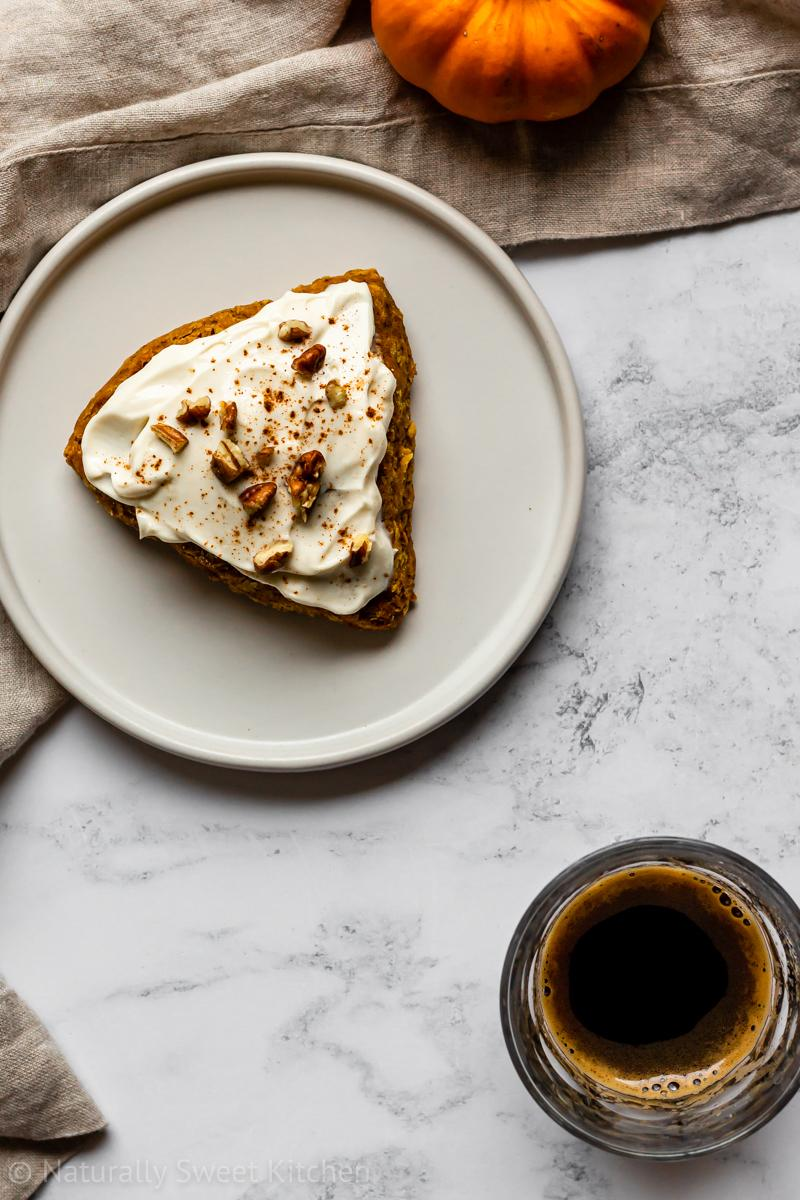 a pumpkin scone topped with maple cream cheese frosting and chopped pecans on a white plate surrounded by a munchkin pumpkin and an espresso glass
