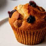 a refined sugar free cranberry muffin with white chocolate chips on a white plate