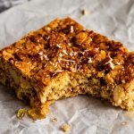 a slice of honey flapjack with a bite taken out of it topped with crushed almonds on a crinkled piece of parchment paper