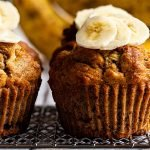 two healthy banana muffins topped with walnuts and banana slices on a silver wire serving rack