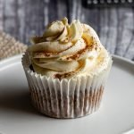 a refined sugar free carrot cake cupcake sits topped with orange buttercream frosting sits on a white plate