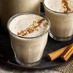 two servings of apple smoothie on a metal serving tray topped with cinnamon and oats