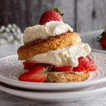 a strawberry shortcake on top of two white plates with floral designs