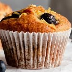 a lemon blueberry muffin on a serving rack topped with lemon zest