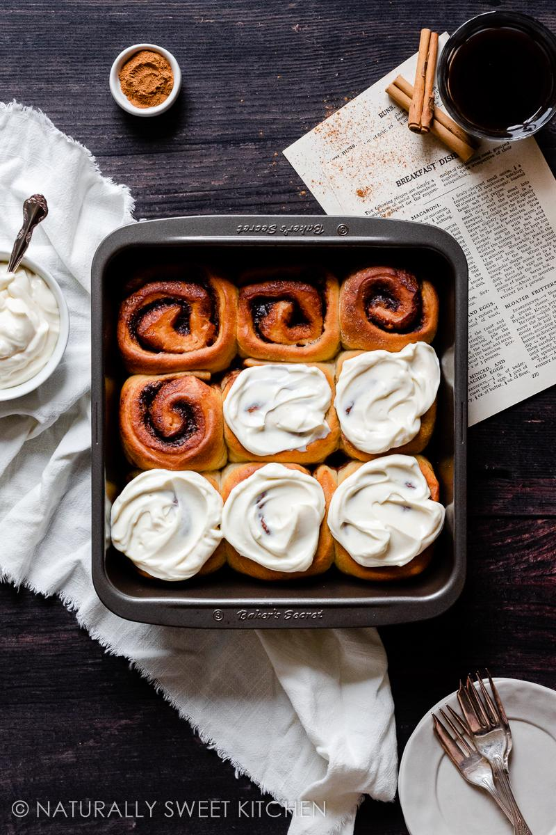 a tray of warm healthy cinnamon rolls have been placed on a wooden table surrounded by a bowl of maple cream cheese glaze, recipe pages, cinnamon sticks and a glass of black espresso