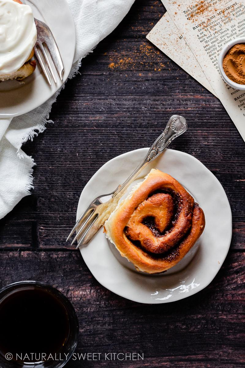 a healthy cinnamon roll sits on a cream coloured plate with a silver fork next to it and a glass of espresso in the corner