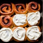 a tray of healthy cinnamon rolls, some topped with maple cream cheese glaze and others are naked.