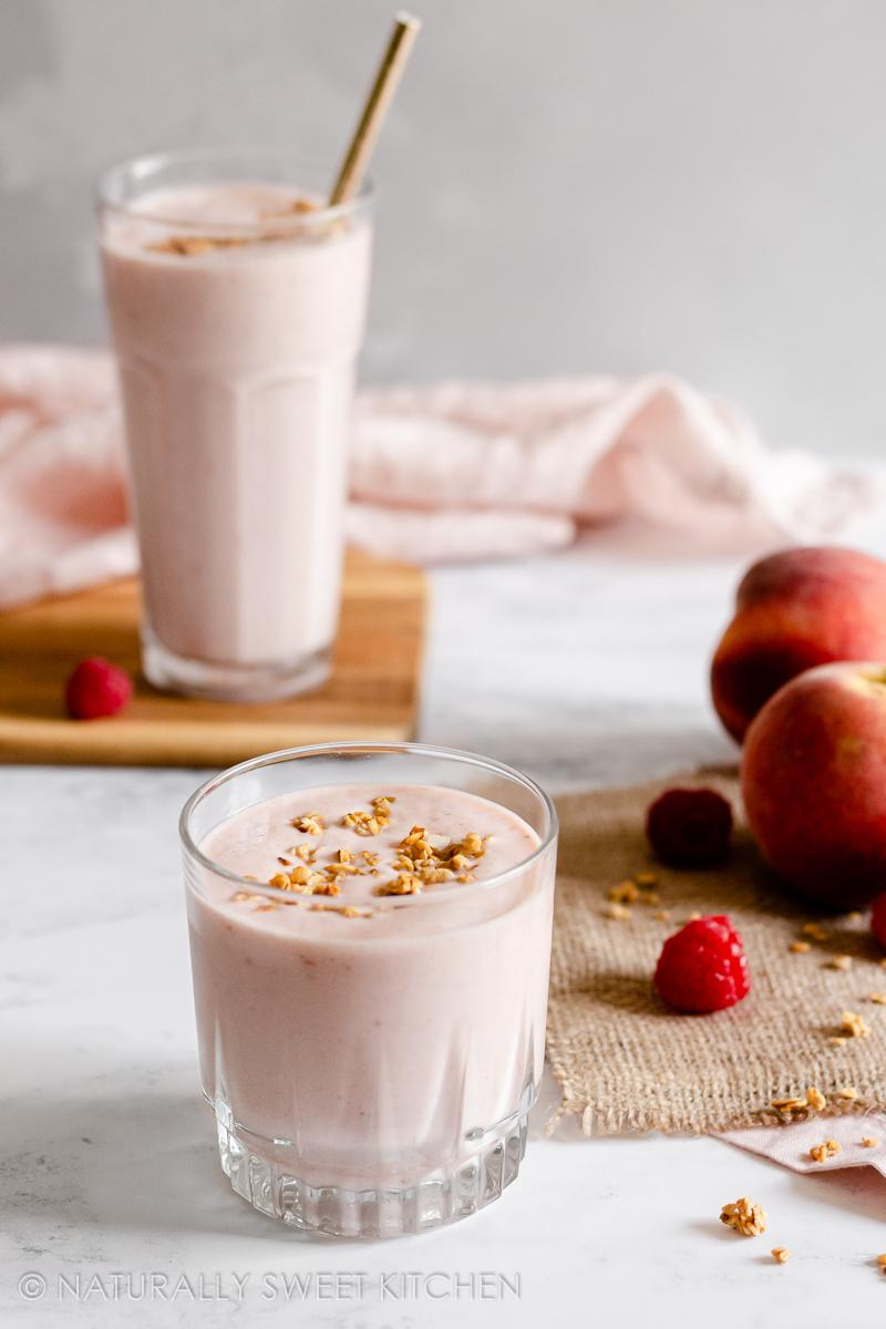two glasses filled with a protein smoothie made with peaches and raspberries on a marble countertop; both are topped with granola and the taller glass in the background has a gold straw in it