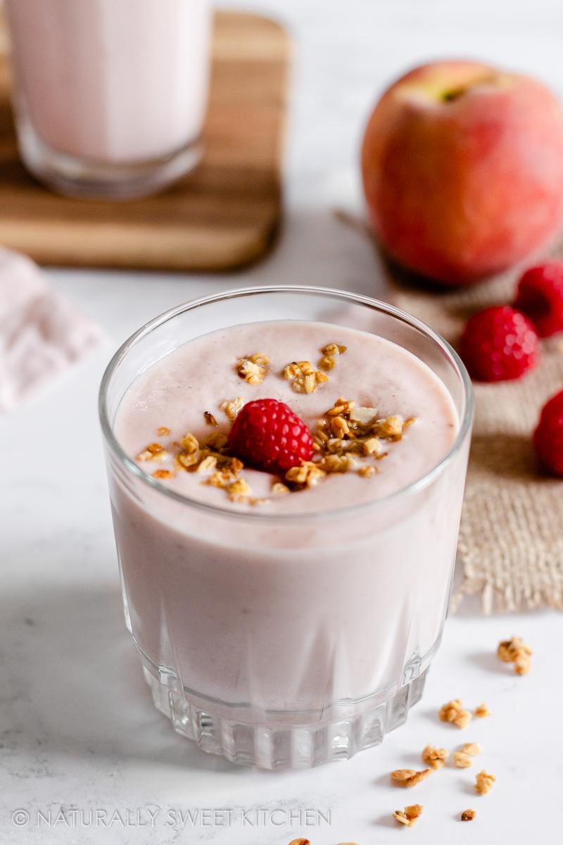 a short glass filled with peach raspberry smoothie topped with granola and a raspberry on a marble countertop