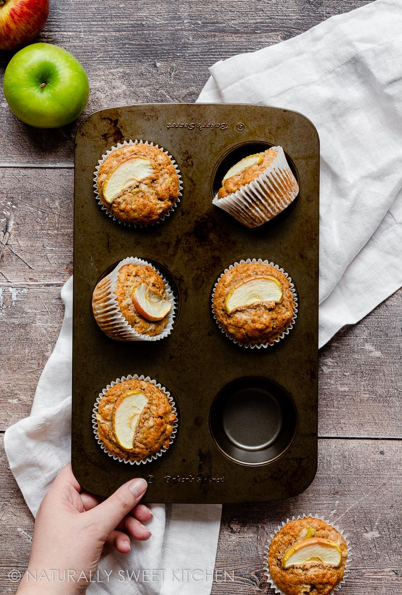 a hand placing down a freshly baked batch of healthy apple muffins on a wooden table with fresh apples in the background