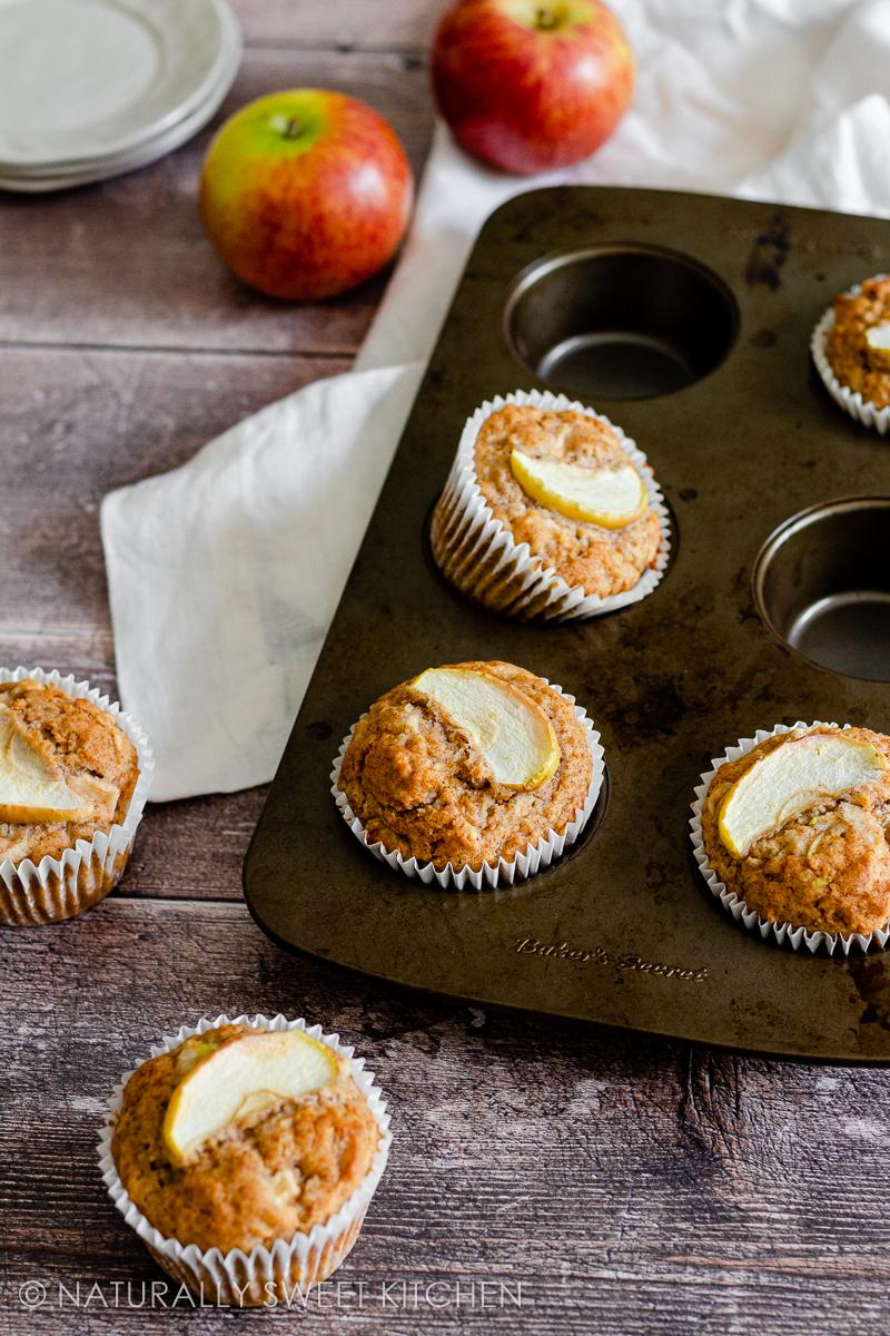 a muffin tray filled with 4 healthy apple muffins sitting on top of a cream linen napkin on a wooden table