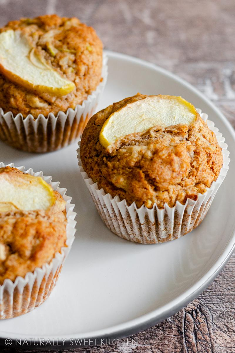three healthy apple muffins topped with sliced apple on a white plate