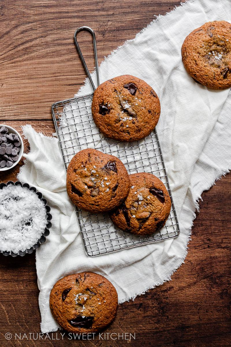 a batch of refined sugar free chocolate chip cookies on a silver cooling rack