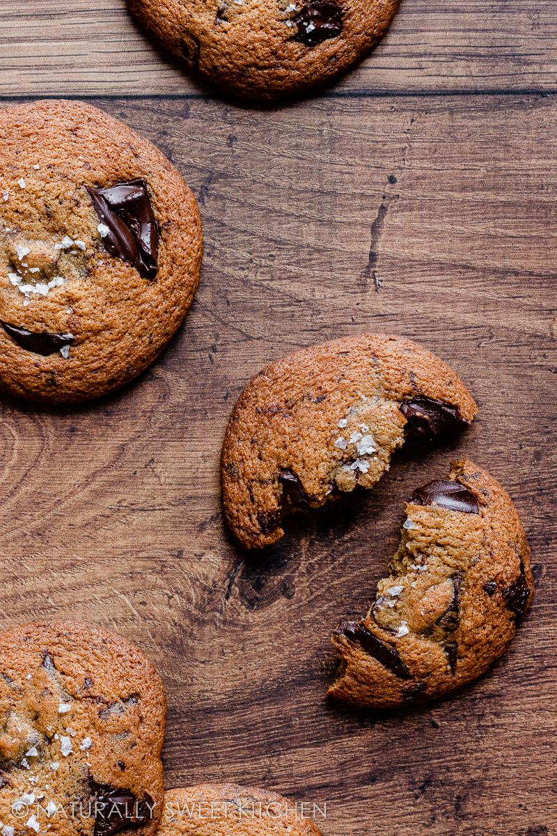a broken chocolate chip cookie on a wooden table surrounded by full cookies topped with sea salt